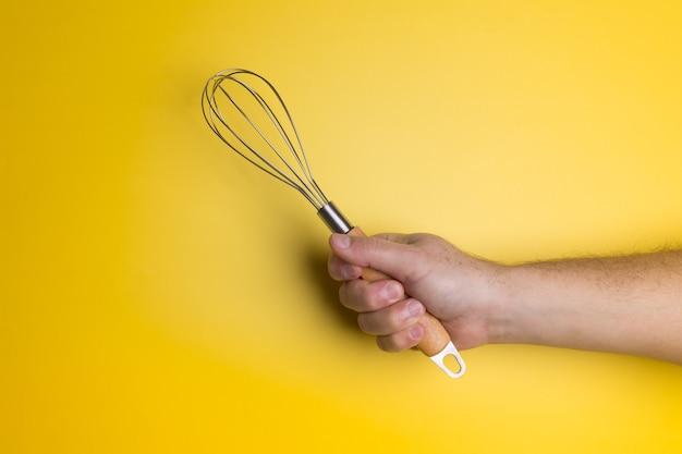 Homme adulte tenant fouet fil fouet sur la gemme de couleur jaune