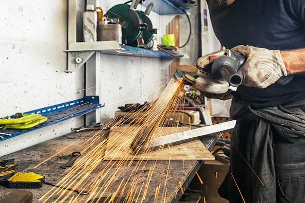Un homme adulte travaillant avec du travail manuel et une meuleuse d'angle en métal