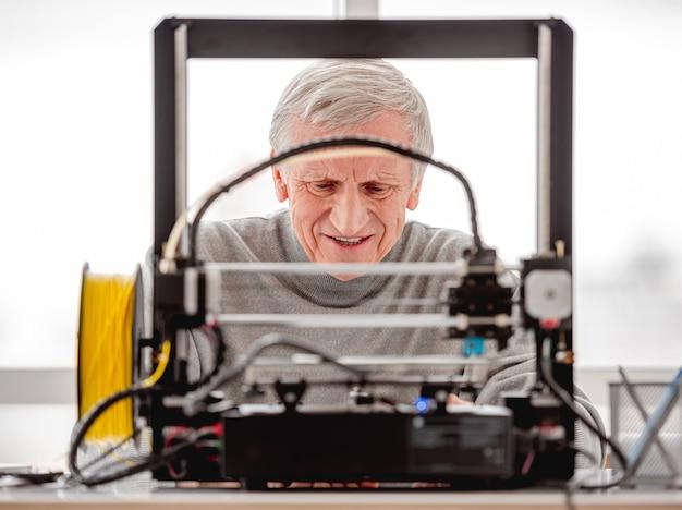 Homme adulte travaillant avec une imprimante 3d en laboratoire avec la lumière du jour et regardant l'appareil