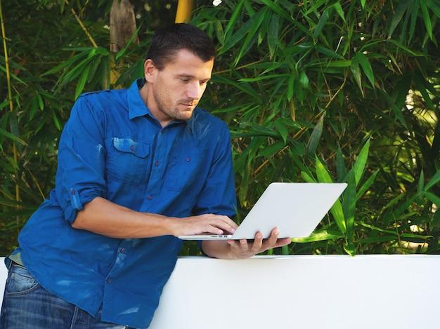 L'homme adulte utilise un ordinateur portable contre les feuilles vertes.