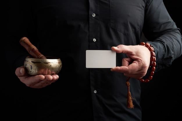 Homme adulte en vêtements noirs tient dans ses mains un bol chantant en cuivre, objet pour rituels religieux, méditations