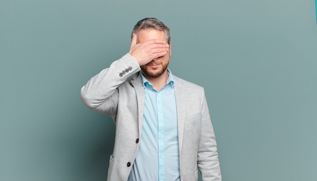 Homme d'affaires adulte couvrant les yeux d'une main se sentant effrayé ou anxieux