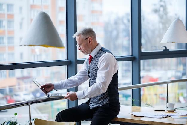 Homme d'affaires adulte, enseignant, mentor travaillant sur un nouveau projet. assis près d'une grande fenêtre sur la table. il regarde l'écran de l'ordinateur portable.
