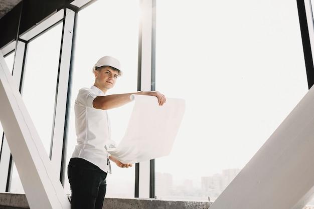 Homme d'affaires adulte équipé d'un casque de protection à la voiture en souriant tout en tenant le plan d'un immeuble en construction près d'une grande fenêtre.