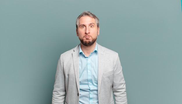 Homme d'affaires adulte avec une expression maladroite, folle, surprise, des joues gonflées, se sentant bourré, gras et plein de nourriture