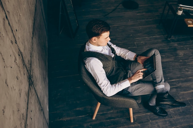 Homme d'affaires adulte masculin assis sur une chaise à son lieu de travail, vérifiant l'augmentation des ventes sur une tablette.