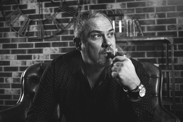 Homme d'affaires adulte sérieux est assis dans son bureau et fume une pipe