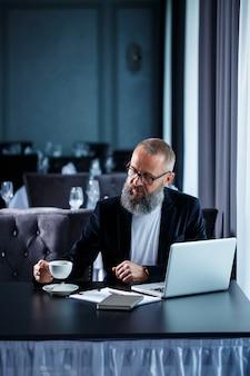 Un homme d'affaires adulte travaille sur un nouveau projet et examine les graphiques de croissance des actions. assis à table près de la grande fenêtre. regarde l'écran de l'ordinateur portable et boit du café.