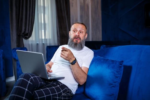 Un homme d'affaires adulte travaille sur un nouveau projet et examine les graphiques de croissance des actions. assis à table près de la grande fenêtre. regarde l'écran de l'ordinateur portable