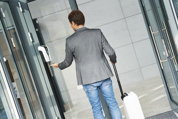 Homme d'affaires adulte et utilisant un désinfectant pour les mains en raison des restrictions de covid-19