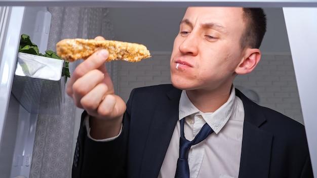 Un homme d'affaires affamé mange du concombre avec des gâteaux dans une cuisine sombre