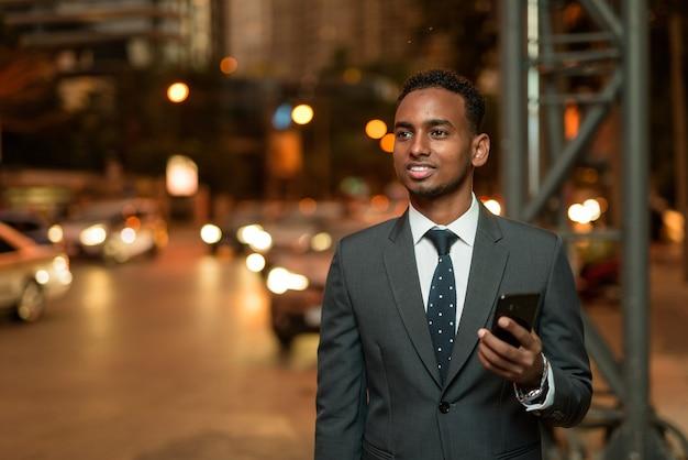 Homme d'affaires africain à l'aide de l'application de téléphonie mobile en attente de taxi la nuit