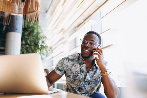 Homme d'affaires africain-américain avec téléphone et ordinateur portable dans un café