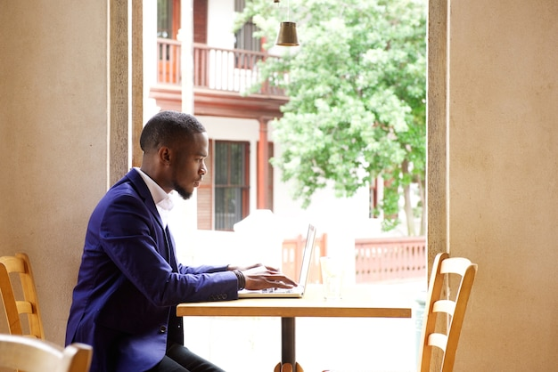 Homme d'affaires africain assis avec ordinateur portable au café
