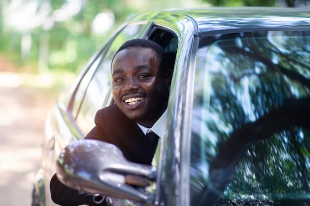 Homme d'affaires africain au volant et souriant tout en étant assis dans une voiture avec une fenêtre ouverte.