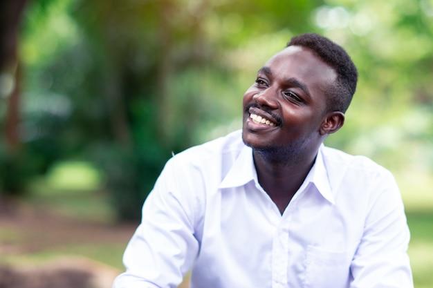 Homme d'affaires africain en chemise blanche, souriant et assis à l'extérieur avec des arbres verts sur fond.