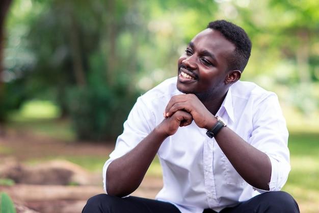 Homme d'affaires africain en chemise blanche, souriant et assis à l'extérieur avec des arbres verts.