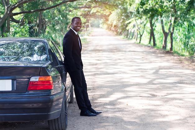 Homme d'affaires africain en costume debout près de la voiture avec un fond naturel vert.