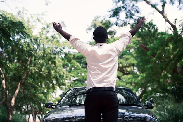 Homme d'affaires africain de liberté en costume debout près de la voiture avec un fond naturel vert.