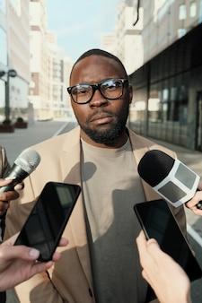 Homme d'affaires africain à lunettes parlant avec des journalistes debout dans la ville