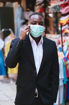Homme d'affaires africain avec un masque médical pour se protéger du virus corona ou covid-19