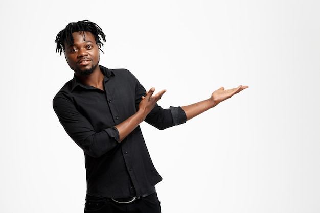 Homme d'affaires africain prospère, pointant les mains dans le côté sur blanc.