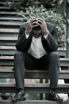 Un homme d'affaires africain sérieux a échoué ou bouleversé son travail et assis sur un escalier. concept de problème commercial.