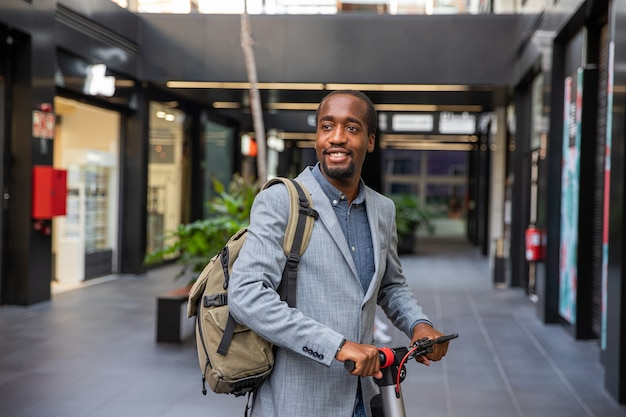 Homme d'affaires africain avec son scooter électrique véhicule non polluant concept de mobilité propre