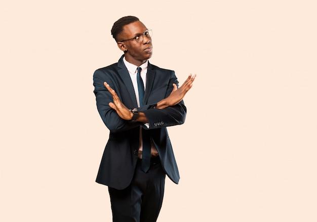 Homme d'affaires afro-américain l'air ennuyé et malade de votre attitude, en dire assez! mains croisées sur le devant, vous disant de vous arrêter contre le mur beige