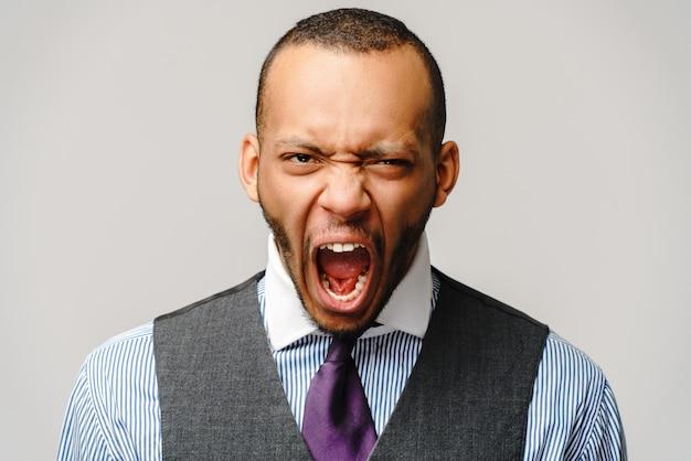 Homme d'affaires afro-américain en colère dans le stress sur un mur gris clair.