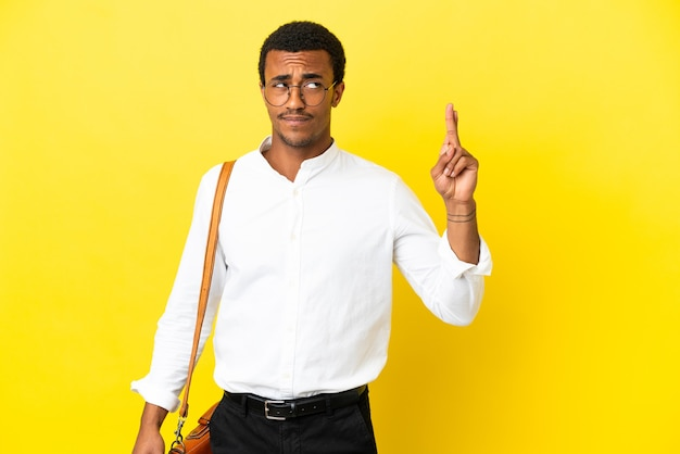Homme d'affaires afro-américain sur fond jaune isolé avec les doigts croisés et souhaitant le meilleur