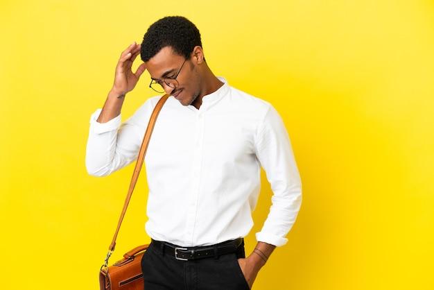 Homme d'affaires afro-américain sur fond jaune isolé en riant