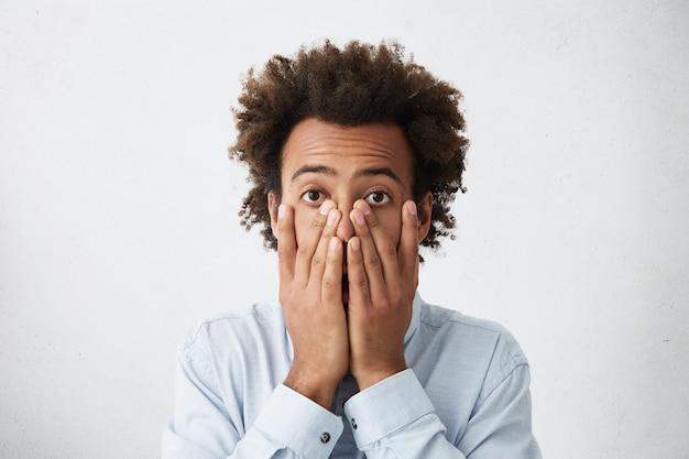 Homme d'affaires afro-américain inquiet couvrant le visage avec les deux mains
