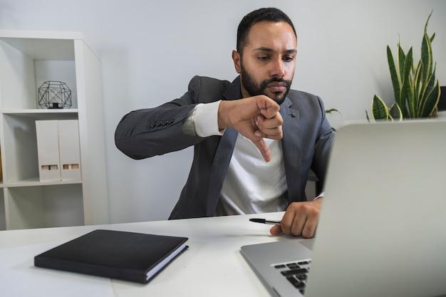 Homme d'affaires afro-américain lors d'un appel vidéo avec ses employés thumbs down technology concept