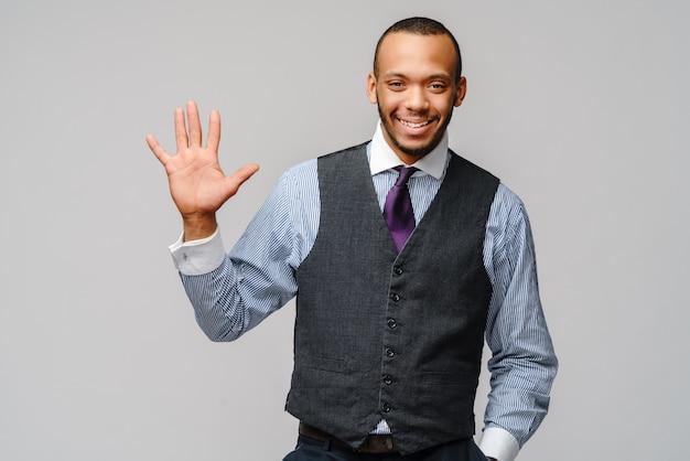 Homme d'affaires afro-américain montrant cinq doigts sur un mur gris