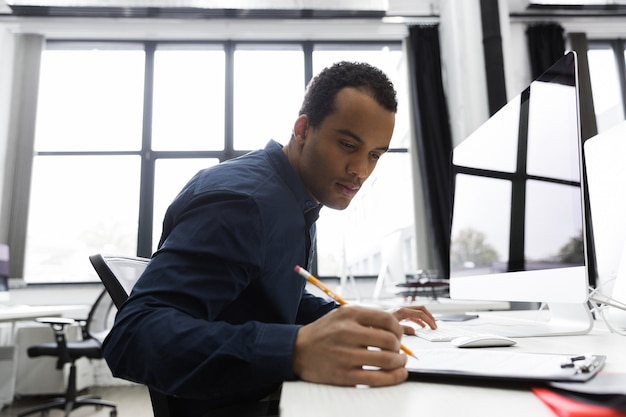 Homme d'affaires afro-américain, prendre des notes tout en étant assis à son bureau