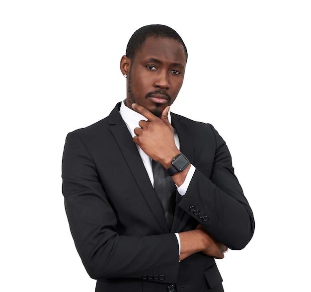 Homme d'affaires afro-américain sérieux touchant le menton portant un costume noir isolé