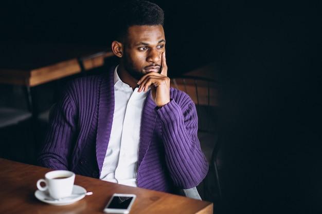 Homme d'affaires afro-américain avec téléphone et café dans un café