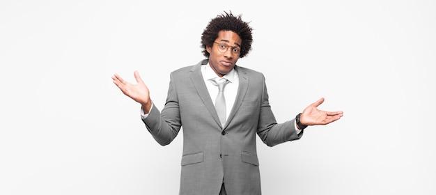 Homme d'affaires afro noir à l'air perplexe, confus et stressé, se demandant entre différentes options, se sentant incertain