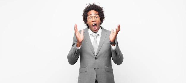 Homme d'affaires afro noir se sentant choqué et excité, riant, étonné et heureux à cause d'une surprise inattendue