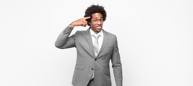 Homme d'affaires afro noir se sentant confus et perplexe, montrant que vous êtes fou, fou ou fou