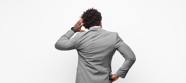 Homme d'affaires afro noir se sentir désemparé et confus, pensant à une solution, avec la main sur la hanche et d'autres sur la tête, vue arrière