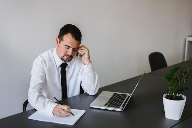 Homme d'affaires âgé assis à son bureau, parler au téléphone et prendre des notes