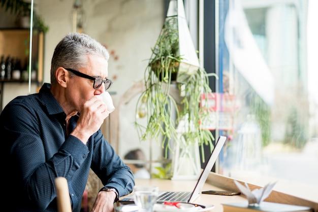 Homme d'affaires âgé ayant un café