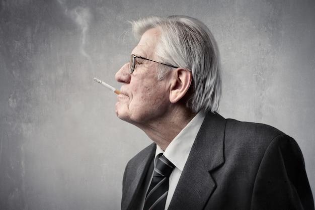 Homme d'affaires âgé fumant