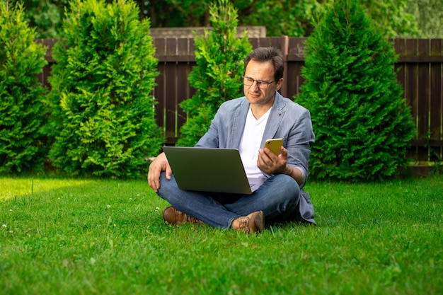 Homme d'affaires d'âge moyen bouleversé travaille avec un ordinateur portable et un téléphone mobile à l'extérieur, est assis sur l'herbe, un employé de bureau masculin triste a perdu son emploi, à la recherche de postes vacants, l'homme a des problèmes avec une entreprise privée, copie espace