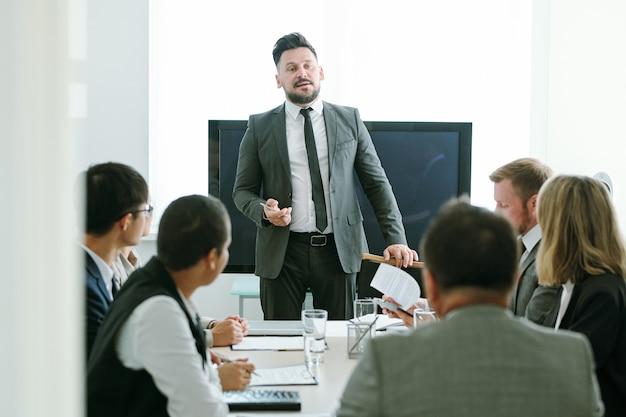 Homme d'affaires d'âge moyen confiant en tenue de soirée debout par table devant ses collègues et faisant rapport ou discours à la formation