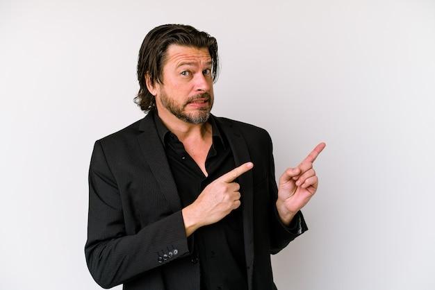 Homme d'affaires d'âge moyen hollandais isolé sur un mur blanc choqué de pointer avec l'index vers un espace de copie