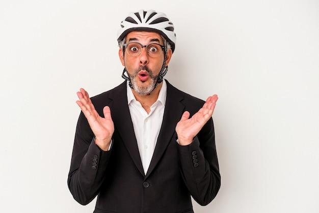 Homme d'affaires d'âge moyen portant un casque de vélo isolé sur fond bleu surpris et choqué.