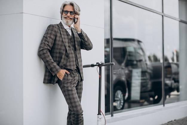 Homme d'affaires d'âge moyen en scooter dans un costume élégant
